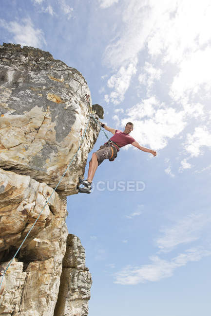 Low angle of climber scaling steep rock face — Stock Photo