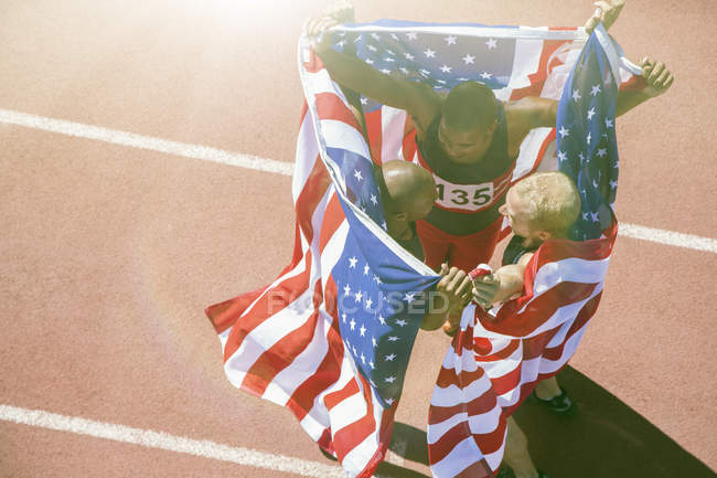 Athlètes tenant des drapeaux américains sur la piste — Photo de stock