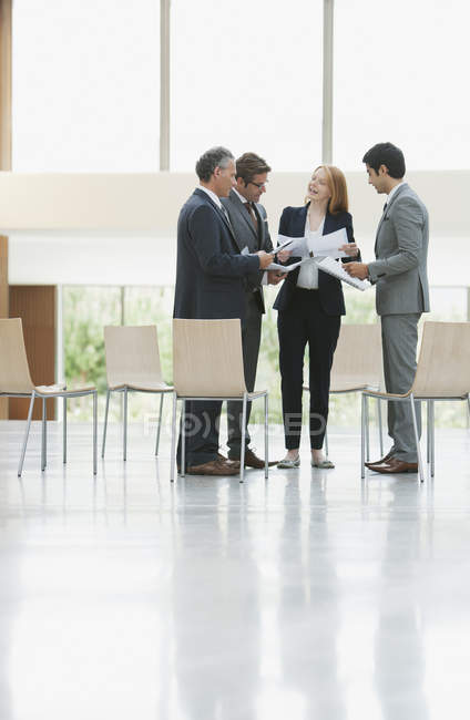 Business people reviewing paperwork in lobby — Stock Photo
