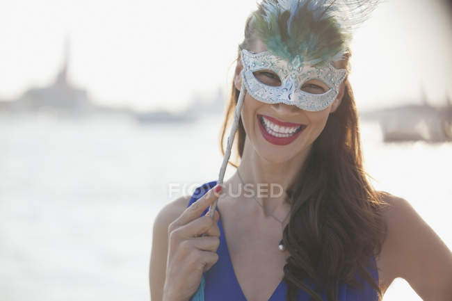 Portrait of smiling woman wearing mask at waterfront in Venice — Stock Photo