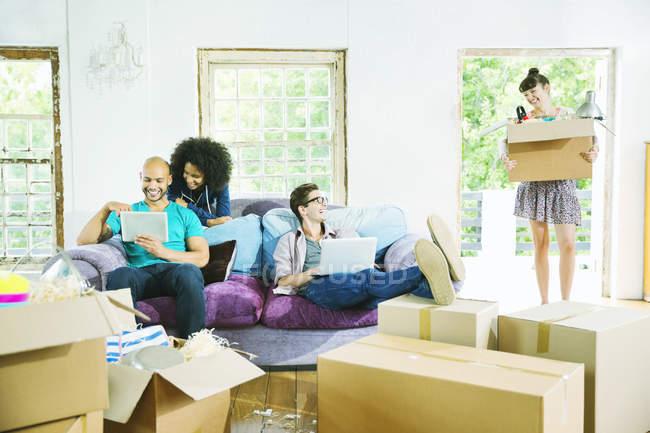 Jovens amigos felizes relaxando em nova casa — Fotografia de Stock