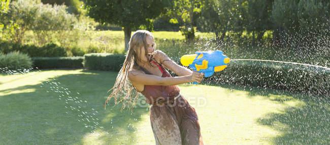 Ragazza che gioca con pistola ad acqua nel cortile — Foto stock