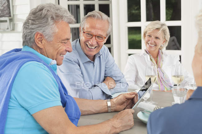 Friends using digital tablet together — Stock Photo
