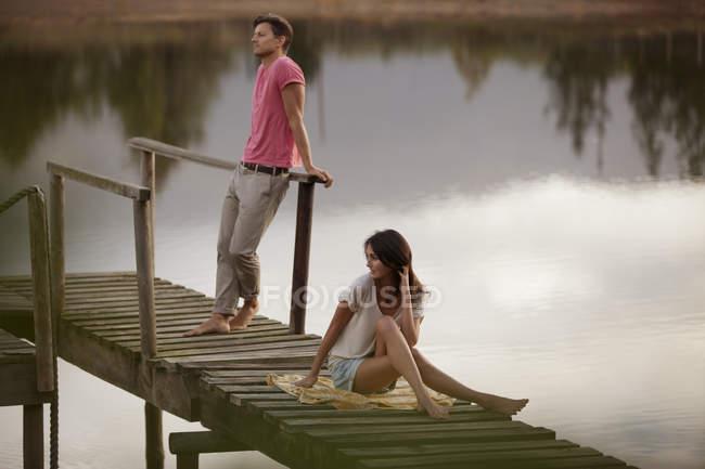 Serene caucasian couple on dock over lake — Stock Photo