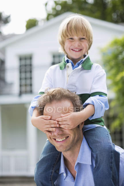 Boy covering father's eyes outdoors — Stock Photo