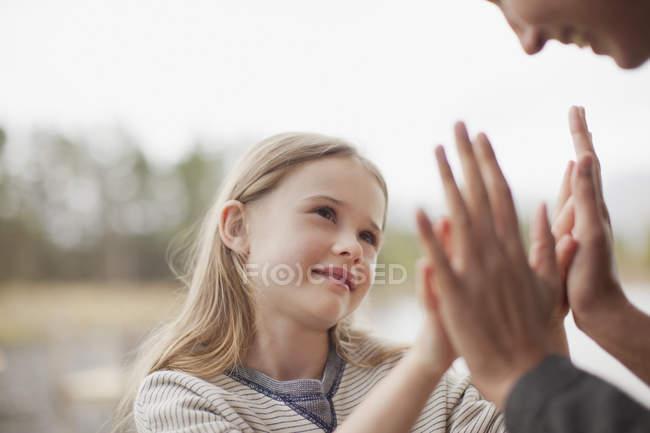 Primer plano de la madre y la hija jugando a la torta - foto de stock