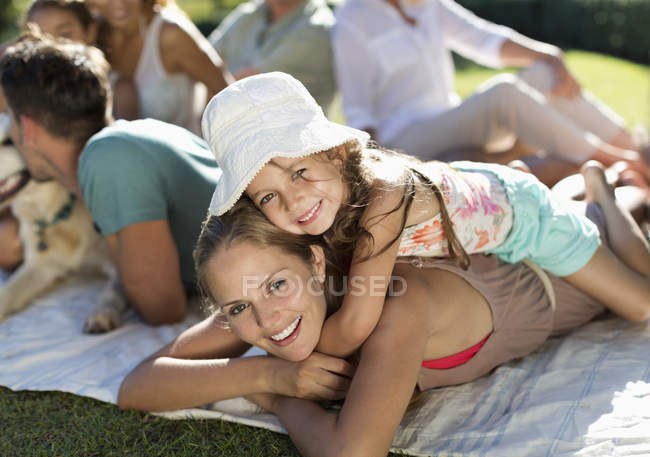Mother and daughter relaxing in grass with family — Stock Photo