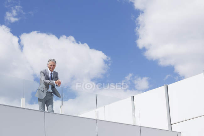 Portrait of confident businessman with hands clasped on balcony — Stock Photo