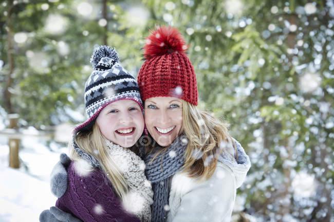 Мать и дочь обнимаются в снегу — стоковое фото