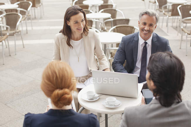 Smiling business people with laptop meeting at sidewalk cafe — Stock Photo