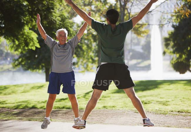 Gli uomini più anziani che fanno salti jack all'aperto — Foto stock