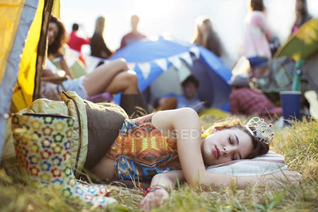 Frau mit Diadem schläft bei Musikfestival im Schlafsack vor Zelten — Stockfoto