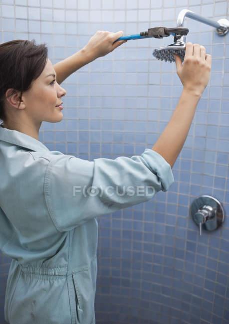 Женщина-сантехник работает над душевой головой в ванной комнате — стоковое фото