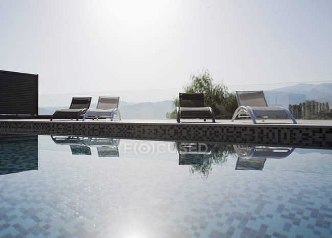 Sun shining over lounge chairs and swimming pool — Stock Photo
