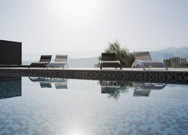 Soleil brille sur les chaises longues et la piscine — Photo de stock