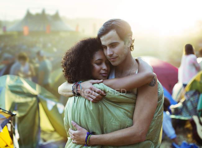 Пара в спальном мешке, обнимающая снаружи палатки на музыкальном фестивале — стоковое фото
