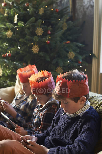 Children in paper crowns relaxing on sofa — Stock Photo