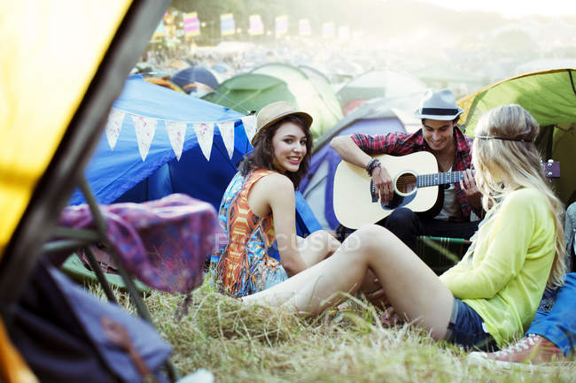 Friends with guitar hanging out near tents at music festival — Stock Photo