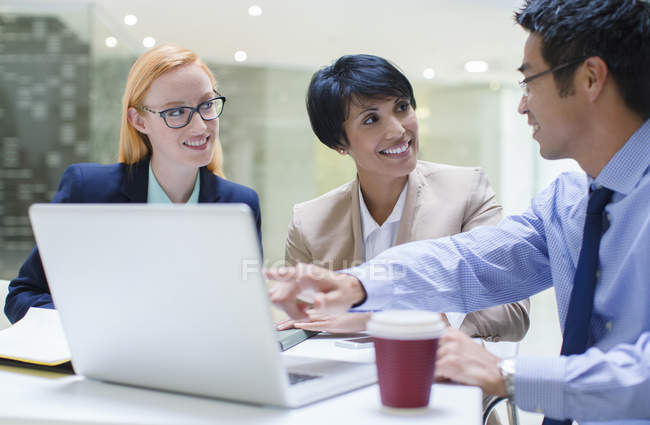 Business people gathered around laptop in office building cafe — Stock Photo