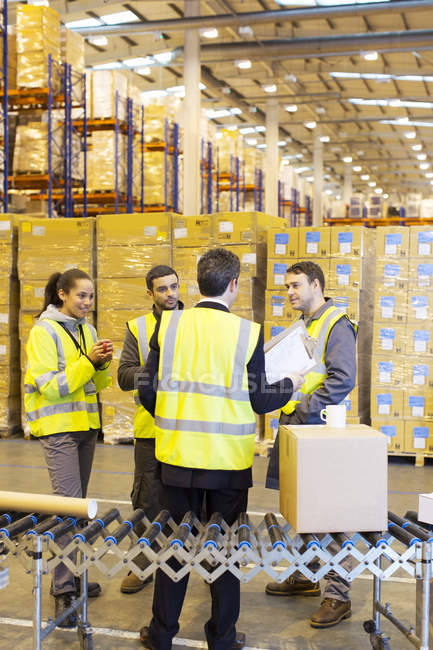 Businessman and workers talking in warehouse — Stock Photo