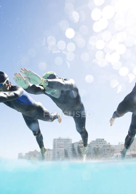 Уверенные и сильные триатлонисты, ныряющие в бассейн — стоковое фото