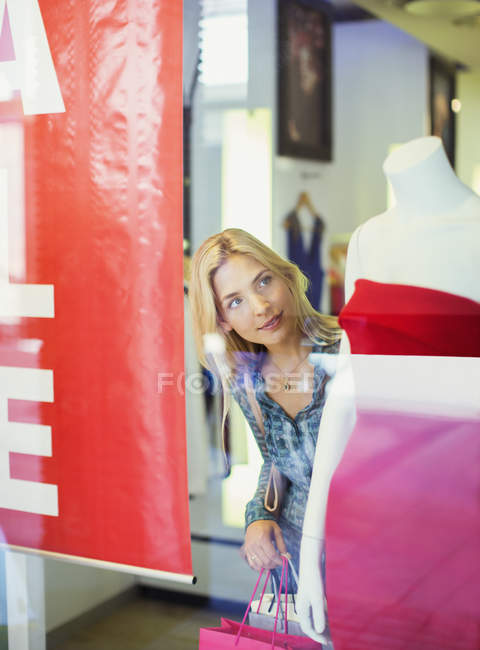 Woman admiring clothes on mannequin in clothing store — Stock Photo