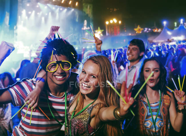 Portrait of friends with glow sticks at music festival — Stock Photo