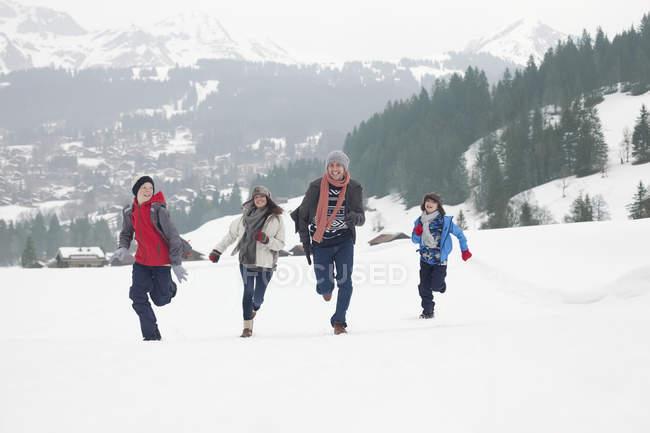 Семья, бегущая на снежном поле — стоковое фото