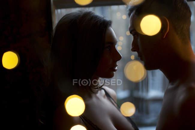 Пара, глядящая друг другу в глаза в темноте — стоковое фото