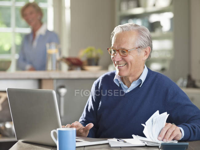 Man using laptop at kitchen table — Stock Photo