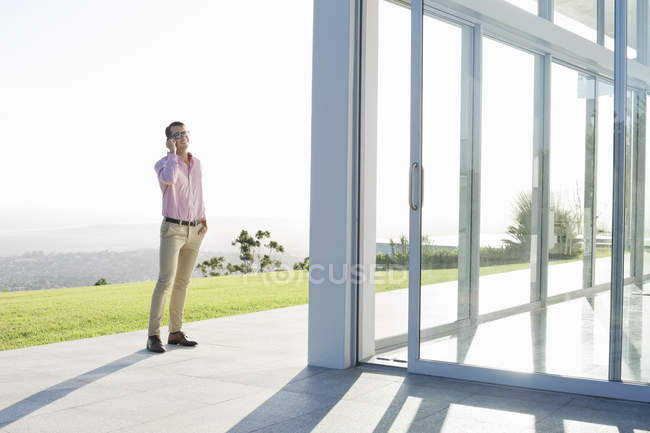 Businessman talking on cell phone outdoors of modern office — Stock Photo