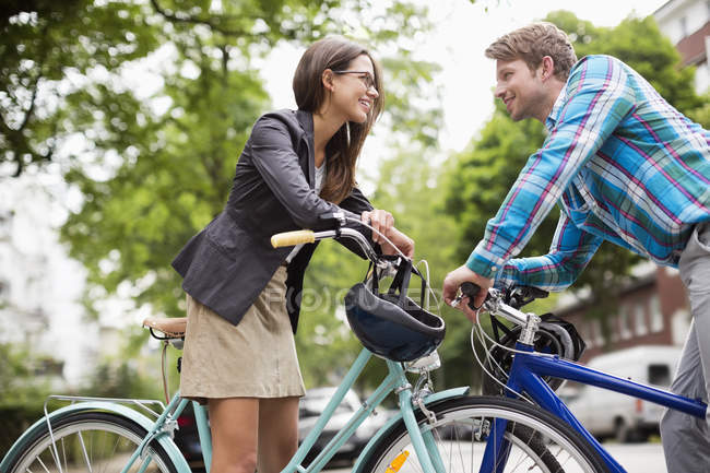 Casal empurrando bicicletas na rua da cidade — Fotografia de Stock