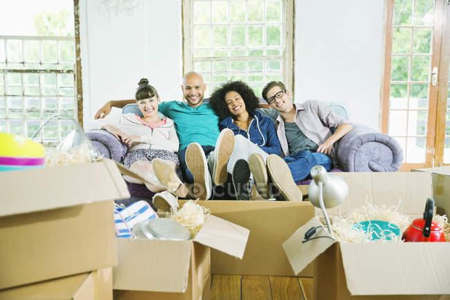 Amigos relajándose juntos en un nuevo hogar - foto de stock