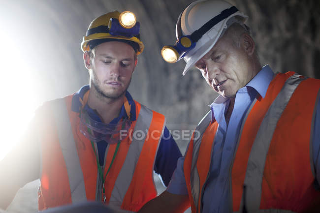 Workers in hard hats talking in tunnel — Stock Photo