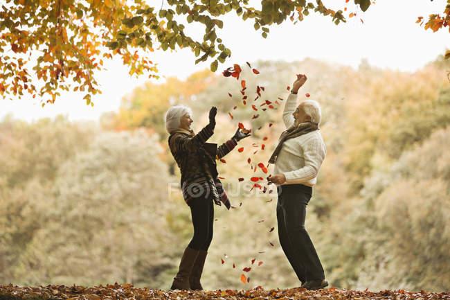 Pareja mayor jugando en hojas de otoño - foto de stock