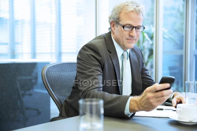 Geschäftsmann SMS mit Handy im Konferenzraum in modernem Büro — Stockfoto