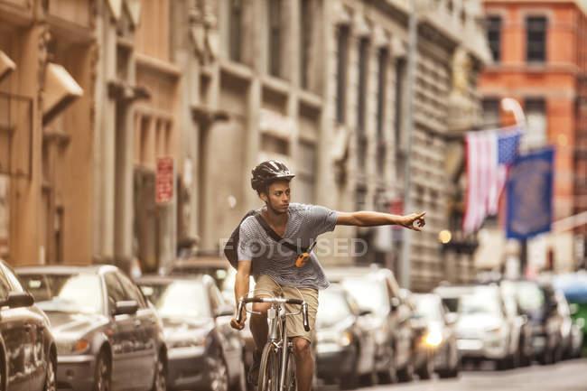 Uomo in bicicletta sulla strada della città e gesticolare turno — Foto stock