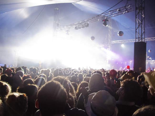 Вентиляторы с видом освещенной сцену на фестивале музыки — стоковое фото