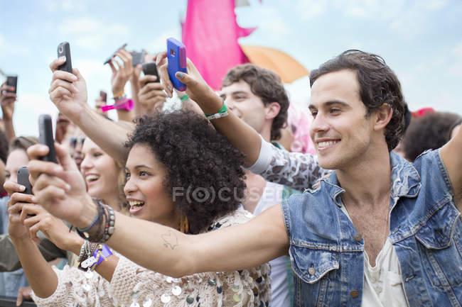Ventilateurs avec des téléphones de caméra acclamant au festival de musique — Photo de stock