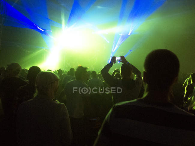 Silhouette of crowd facing illuminated stage at music festival — Stock Photo