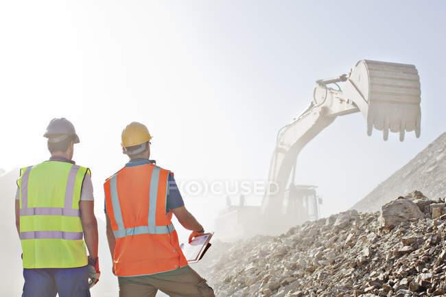 Travailleurs regardant creuseur dans la carrière — Photo de stock