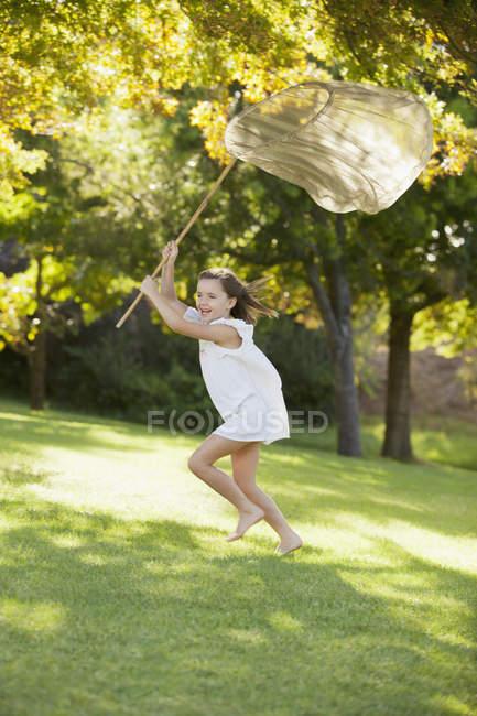 Ragazza felice in esecuzione con rete farfalla in erba — Foto stock