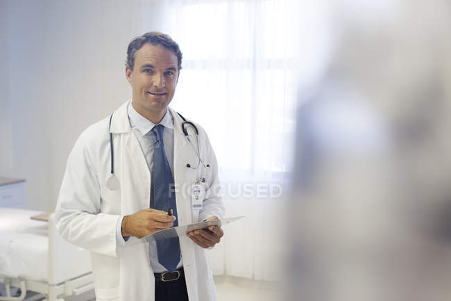 Doctor reading clipboard in hospital room — Stock Photo