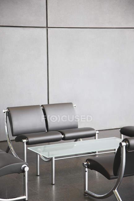Cadeiras e mesa em área de recepção de escritório — Fotografia de Stock
