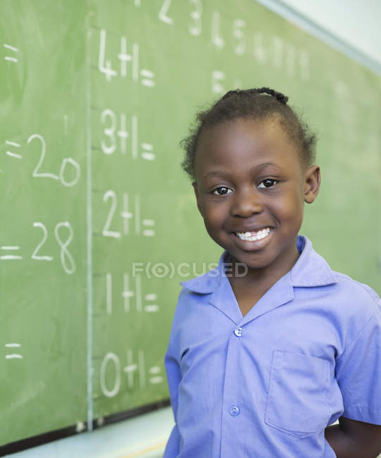 Estudante Africano americano sorrindo para lousa — Fotografia de Stock