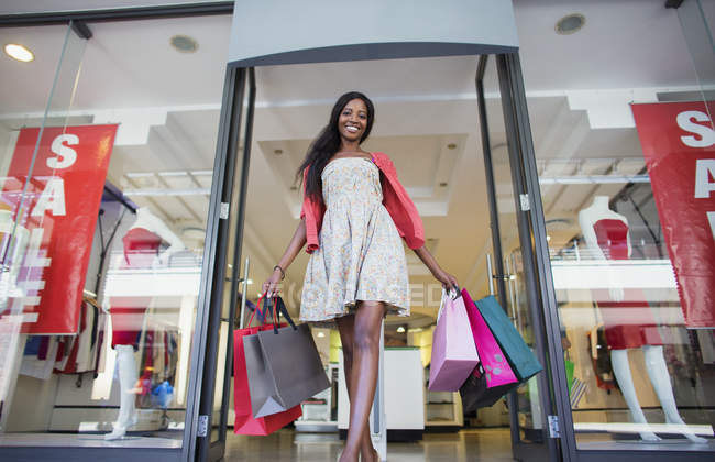 Low angle view of woman carrying shopping bags out of clothing store — Stock Photo