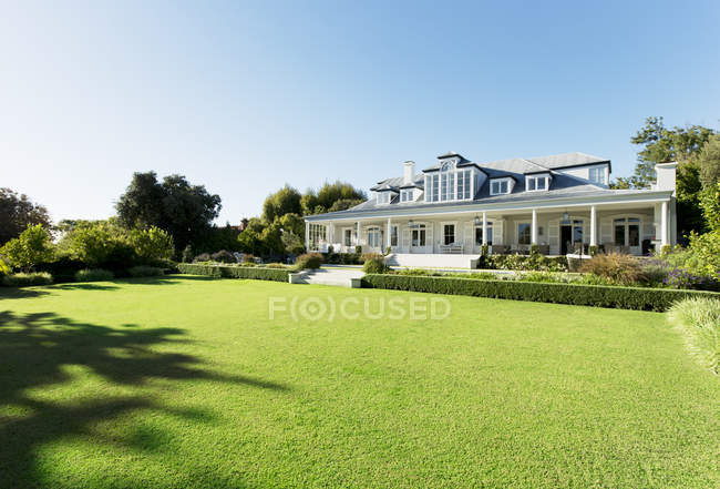 Luxury house facing sunny lawn — Stock Photo