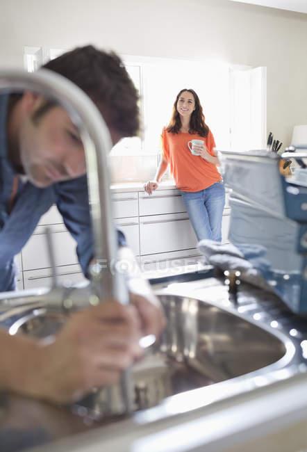 Женщина смотрит, как сантехник работает на кухне раковина — стоковое фото