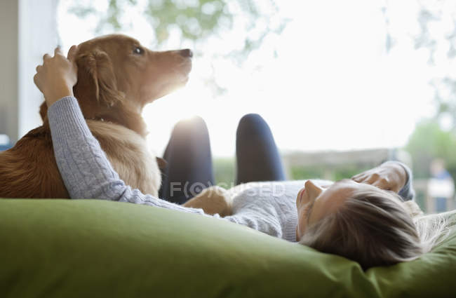 Woman petting dog on bed at modern home — Stockfoto
