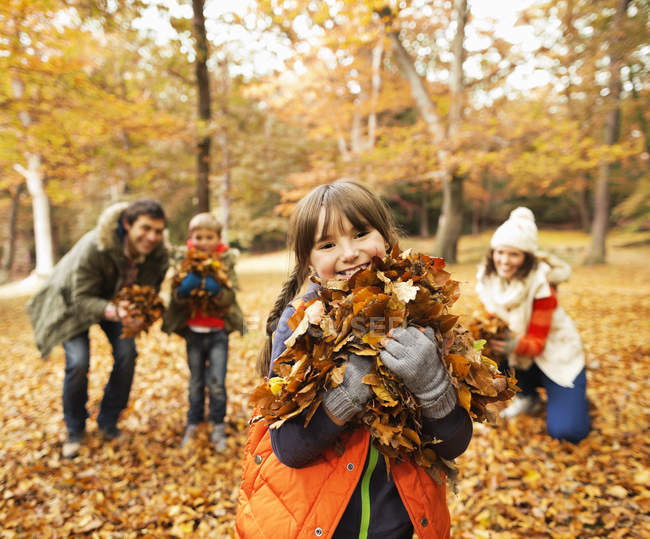 Happy family playing in autumn leaves — Stock Photo